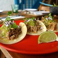 Pork Carnitas Tacos - Pork confit, caramelized with orange juice & Coca-Cola, served with Tomatillo salsa verde, red onions & coriander.